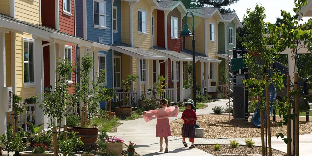 Row houses of bright colors, with two young children playing out front.