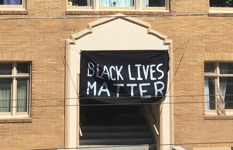 Black Lives Matter banner hangs on the front of a brick building